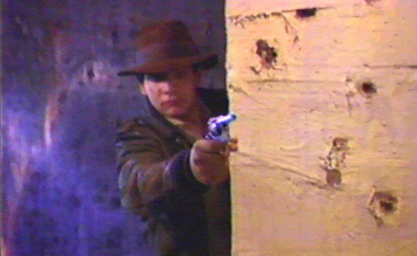 Chris Strompolos as Indiana Jones shoots from cover in the adaptation of Raiders of the Lost Ark in Drafthouse Films' Raiders! Courtesy of Drafthouse Films.